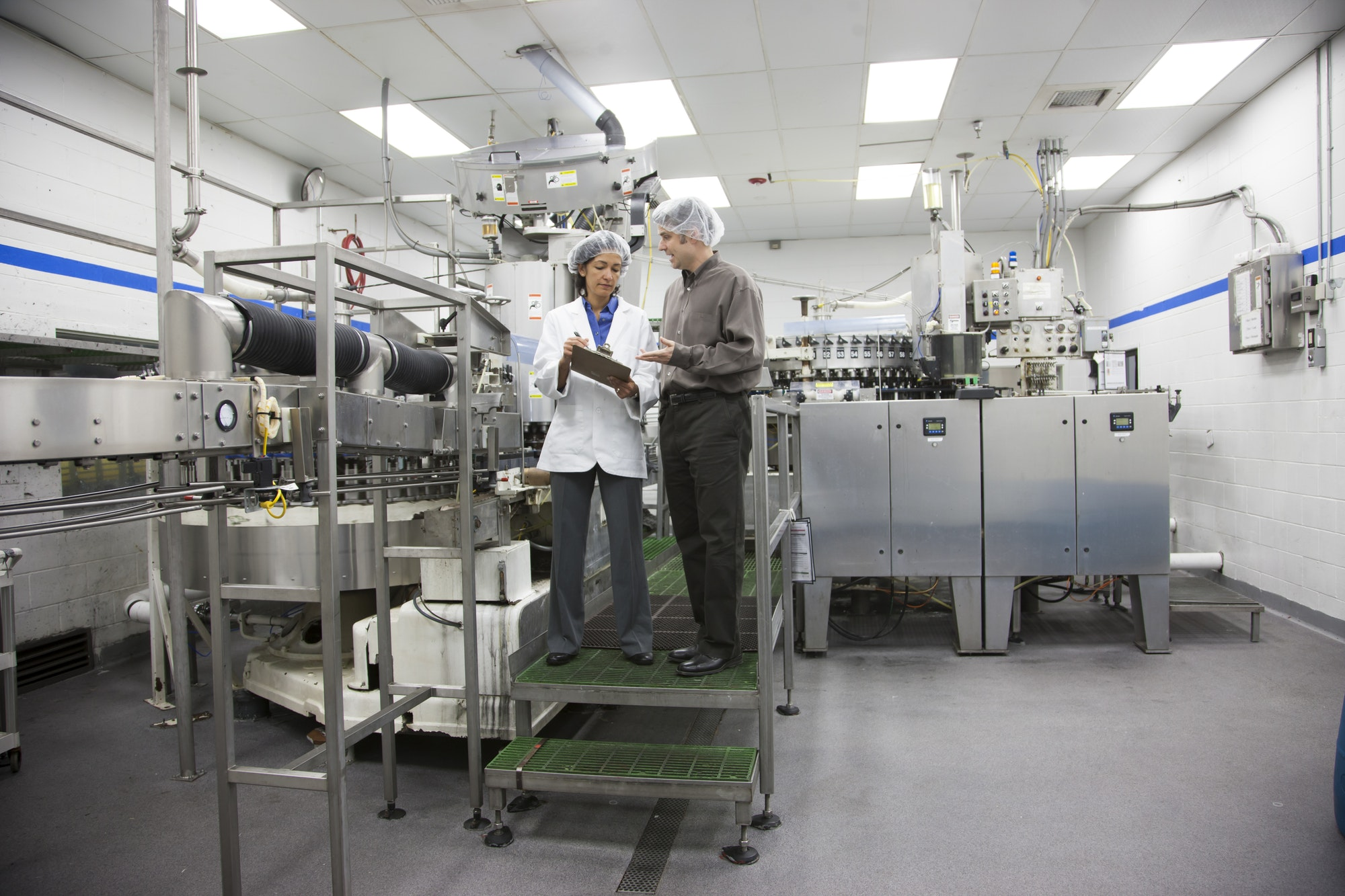 A discussion between a management person and a technician in a bottled water plant.